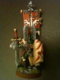 Der Kompaniemeister hat an seinem rechten (vom Betrachter seinen linken) Knieschutz das Symbol der Fünften Kompanie der Dark Angels!