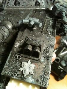 An der linken Seite des Rumpfes wurde der fehlende Nebelwerfer (aus dem Bausatz des Imperialen Baneblades) angebracht, sowie das Nurglesymbol der Death Guard aus dem CSM Fahrzeuggussrahmen.